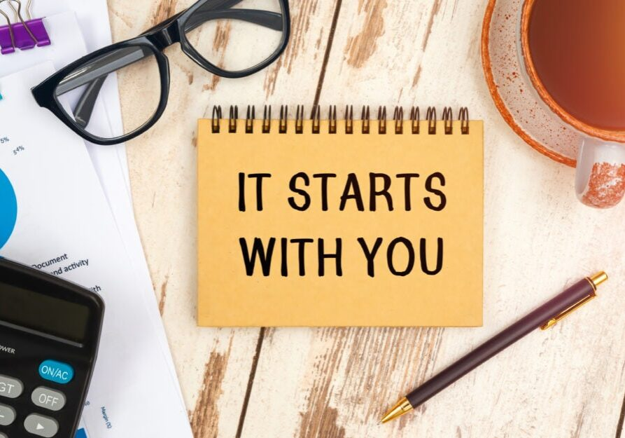 IT STARTS WITH YOU is written on a notepad on an office desk with office accessories.